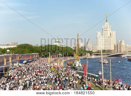Finishing of Immortal Regiment procession in Victory Day - thousands of people marching along the Moskva River embankment in the direction of the skyscraper of the Stalin era with flags and portraits in commemoration of their l