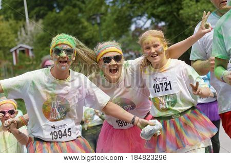 STOCKHOLM SWEDEN - MAY 22 2016: Three smiling women and girl covered with green color dust in the Color Run Event in Sweden May 22 2016