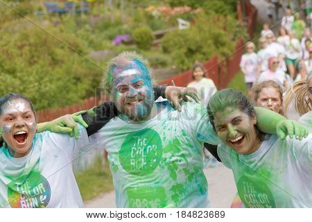 STOCKHOLM SWEDEN - MAY 22 2016: Three smiling women and man covered with colorful color dust in the Color Run Event in Sweden May 22 2016