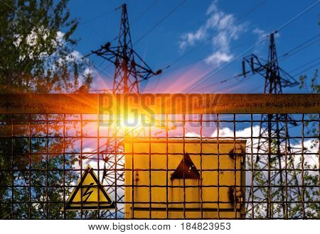Sign dangerously high voltage on the background of high-voltage lines at sunset