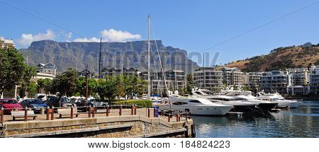 Cape Town, South Africa May 20, 2016: Cape Town and coast line, jetty. Are ships and boats, far mountain on the blue sky background. Summer. South Africa