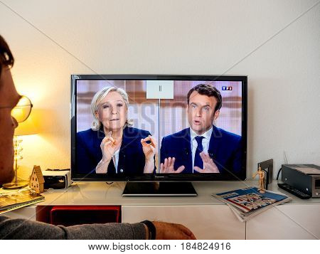 PARIS FRANCE - MAY 03 2017: Supporter of admiring one of the future President of France at the TV debate between Emmanuel Macron and Marine Le Pen on a home TV screen on May 03 2017 in Paris France. France will hold the second round on May 07 2017