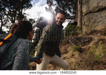 Hiker Helping His Girlfriend Uphill On Country Path.