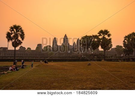 ANGKOR WAT CAMBODIA - JANUARY 28 2015: Tourists waiting for dawn at Angkor Wat temple in Cambodia. Angkor Wat is the largest Hindu temple complex and religious monument in the world