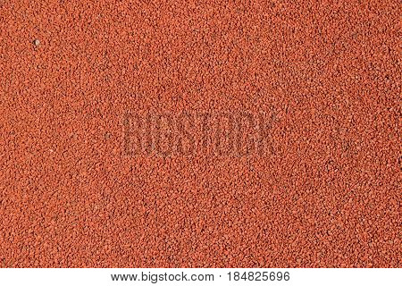 The Texture of a rubber crumb, rubber asphalt, is used in stadiums for running track. Red background.