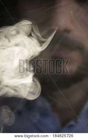 Man Vaping Electronic Cigarette With Clouds.