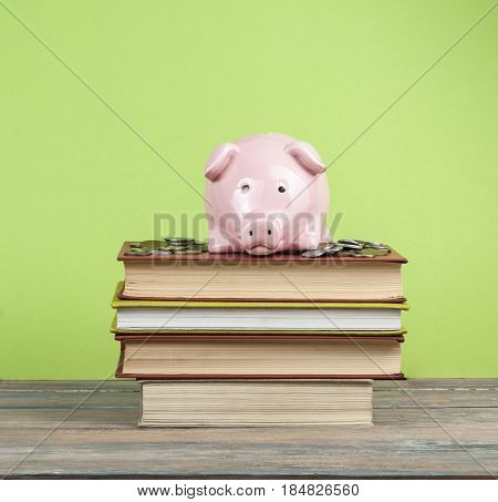 Pink piggy bank with colorful books on wooden table. Concept of funding education.
