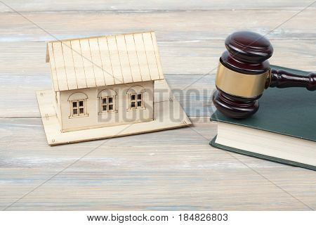 Model house with judge gavel on wooden background. Law concept.