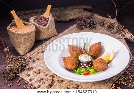 Fried meat meatballs from stewed grains of wheat with stuffing of mutton forcemeat, onions and pine nuts