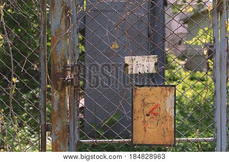 Abandoned place. Danger. Fence from the grid overgrown with branches. There is a lock on the door.