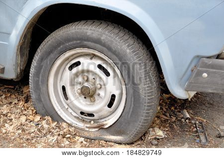 A car with an emergency standing for a long time in the fall unattended with a flat tire