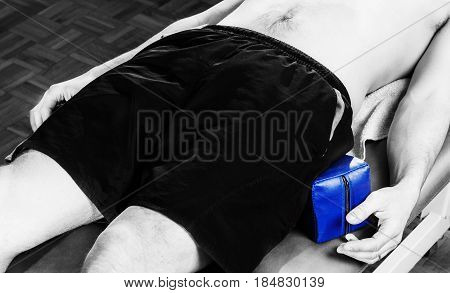 Male Patient In Stretcher With Wedges For Postural Protection Of Sacroiliac In Silhouette Studio On