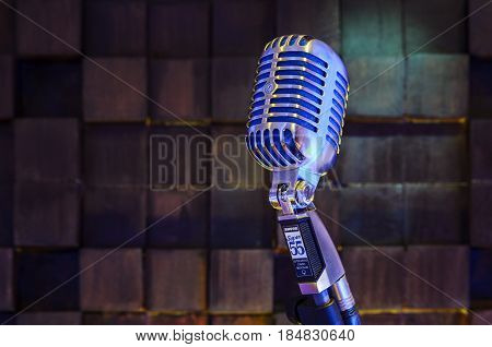 MINSK BELARUS - SEPTEMBER 29 2015: Silver old fashioned stage microphone- SHURE Super 55 Deluxe against wood background. Voice recording concept Retro style mic ready to rock