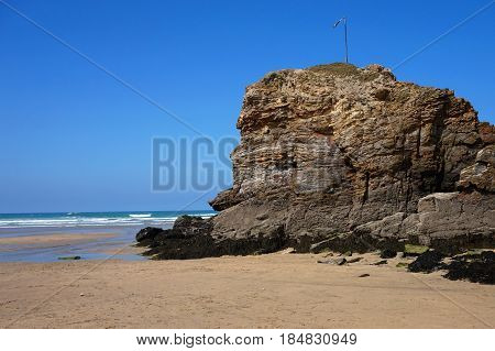 Rocky outcrop on a sandy beach with sea and surf in distance under blue sky
