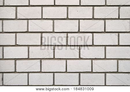 Brick wall of white brick. Brick masonry with smooth seams. Accurate brickwork. White brick wall texture. Building of white brick.