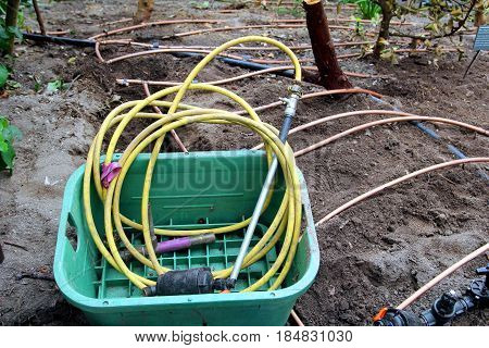 Garden hose and horticultural irrigation pipes on soil