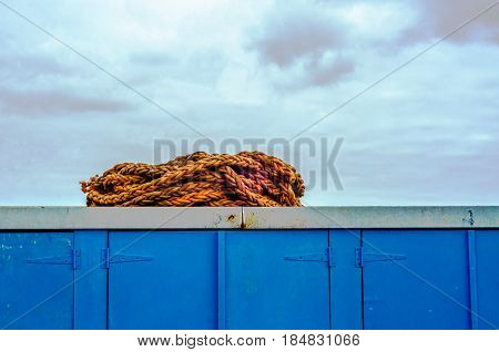Old rope lying on a blue container in a fishing port industry equipment seaside spot ocean