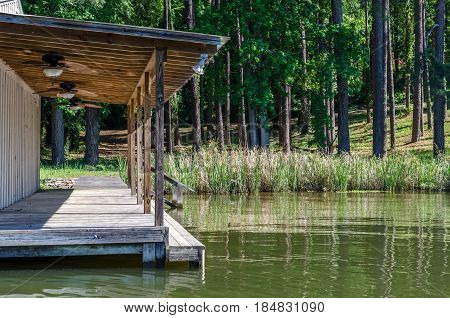 Boat house floating on reflective lake.  Scenic woods, trees and grass with recreational dock for relaxing, swimming or fishing.  Scenic travel destination.