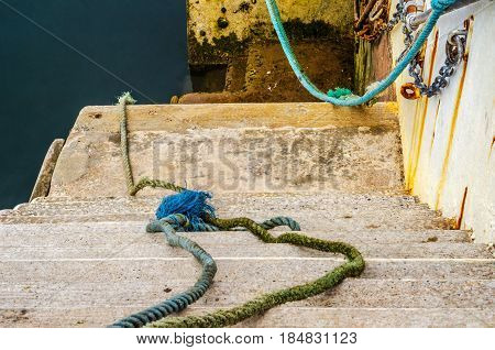 Descent Down To The Ocean In A Fishing Port, Old Cords And Ropes, Industry Equipment, Seaside Town