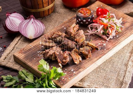 Fried mutton sunflower seeds, are served with sauce ajika and vegetables