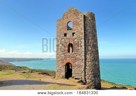 Derelict abandoned Cornish tin mine building on coast path with sea and blue sky in distance