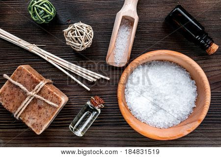 spa cosmetics set with soap, salt, oil on wooden desk background top view