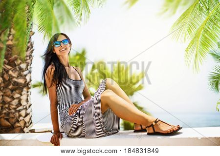 Summer vacation. Beautiful girl under branches of the palm trees by the sea