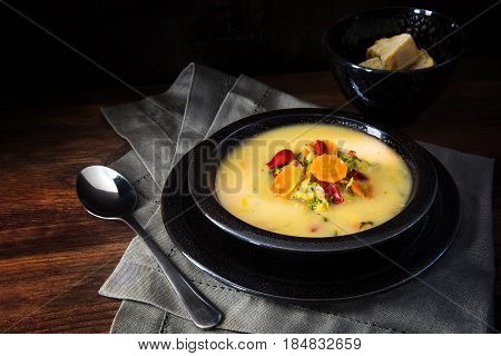 Vegetable cream soup with carrots red peppers and leeks in a black speckled bowl on brown rustic wood dark background with copy space selective focus