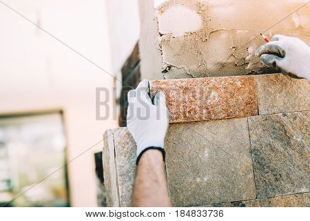 Worker Installing Stone Tiles In Construction Site. Masonry Details On Exterior Wall With Trowel Put