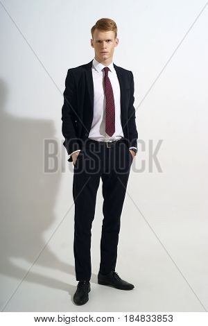 Young handsome man with red hair in black classical formal suit, white jacket and red tie