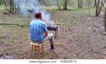 Man Is Sitting In The Woods Near A Smoking Brazier