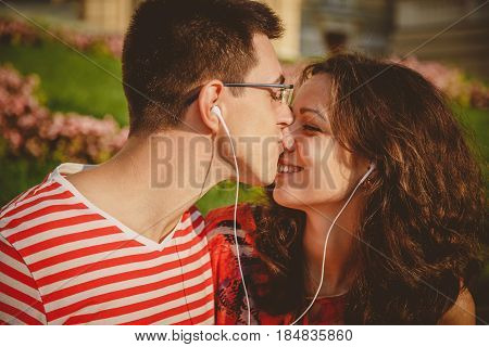 Happy Couple With Earphones Sharing Music From A Smart Phone In Park Outdoors. Man Is Kissing His Gi