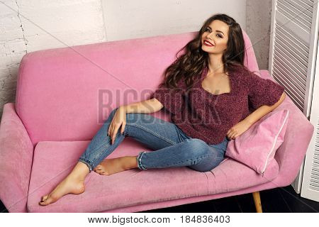 Fashionable classy stylish girl in blue jeans and purpple pullover sitting at pink sofa. Stunning beautiful pretty happy smiling girl with long curly hair and red lips looking at you
