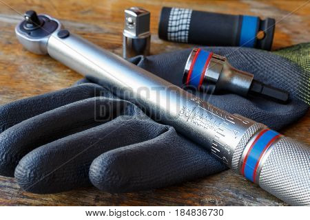 Torque wrench with spanner heads and work glove on the table in a workshop