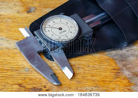 Slide caliper with a round dial in a storage case