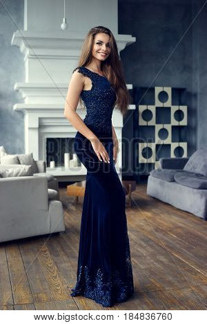 Gorgeous tall slim glamorous woman in long blue lace luxury evening dress standing in lounge interior with wooden floor. Brunnette beautiful stunning girl looking at you. Vogue style portrait