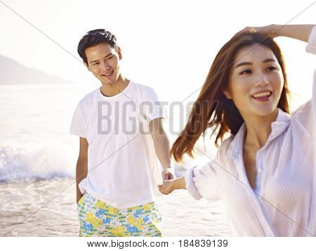 young loving and happy asian couple holding hands on beach.
