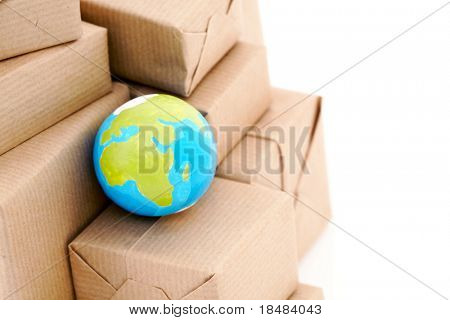 Earth globe on a heap of packets wrapped with some kraft paper