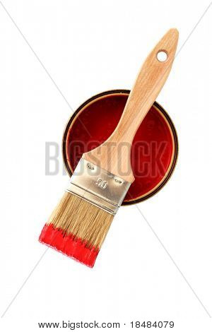 Brush of red painting put down in the middle of a pot of painting on white background