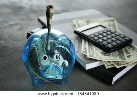 Composition of piggy bank with dollars, notebooks and calculator on grey table