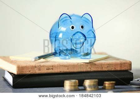 Composition of piggy bank, coins and stationery on light background