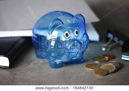 Composition of piggy bank and coins on grey table