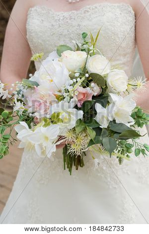 Wedding bouquet held by the bride made up of fake flowers but looks like real florals.
