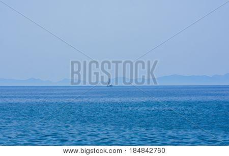 Faraway sailing boat on the blue sea