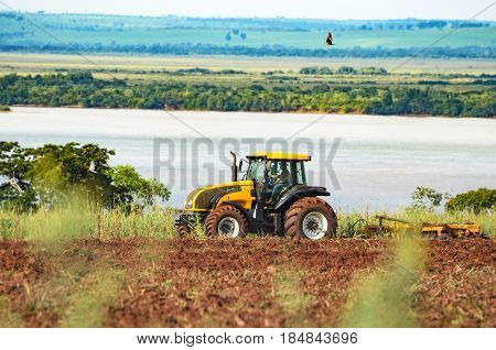 MATO GROSSO DO SUL BRAZIL - APRIL 18 2017: Tractor driver driving a yellow Valtra tractor and plowing the ground for a future plantation. Tractor on a farm with parana river on background.