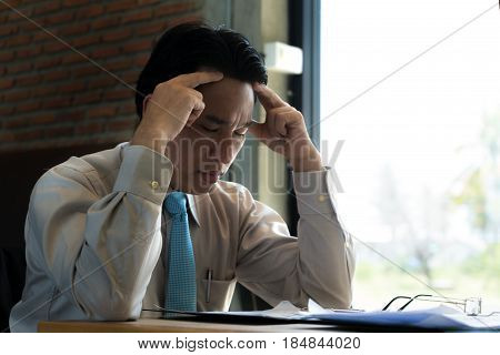 Asian businessman sitting and thinking in cafe looking frustrated and depressed.