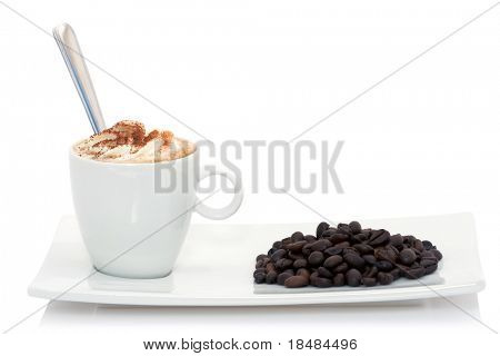 cappucino on a plate with coffee beans