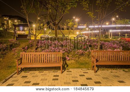 Night scene of wooden park benches at a lakeside park in a small town in South Korea