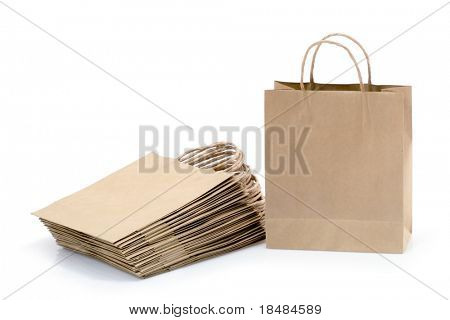 Pile of reusable brown shopping or carrier bags, isolated on white background.
