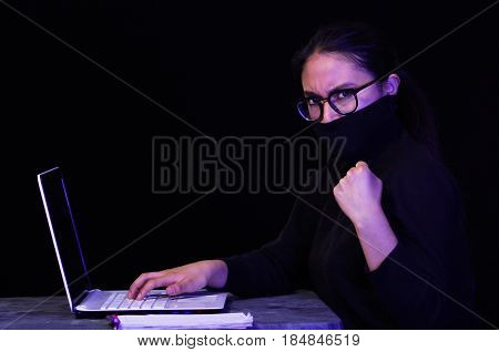 Portrait of a hacker with laptop on dark background using glases while she is working.
